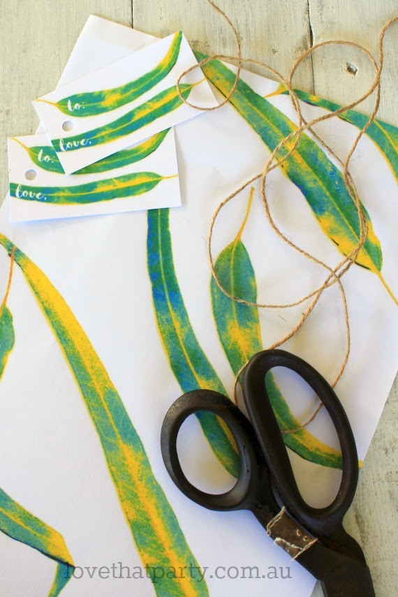 image of bright gum leaf gift wrap paper and gift tags with scissors and twine