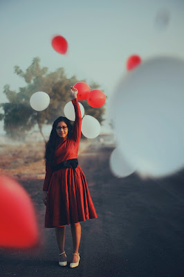 young brown-skinned woman in red dress, black belt, and white shoes releases red and white balloons
