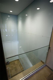 GLASS RAIL OVERLOOKING PAINTED GLASS STAIRWELL
