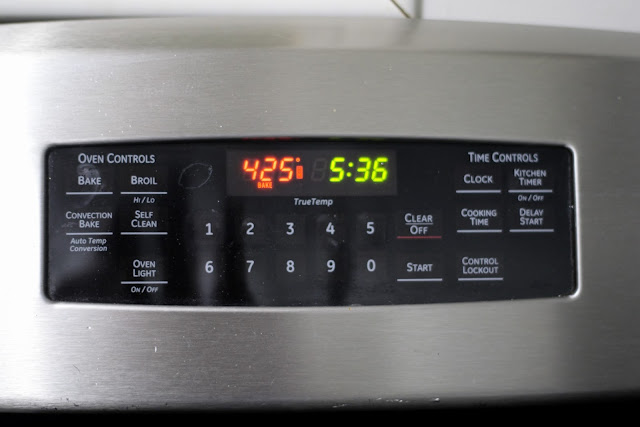 The thermometer on the oven showing that it has been heated to 425 degrees.
