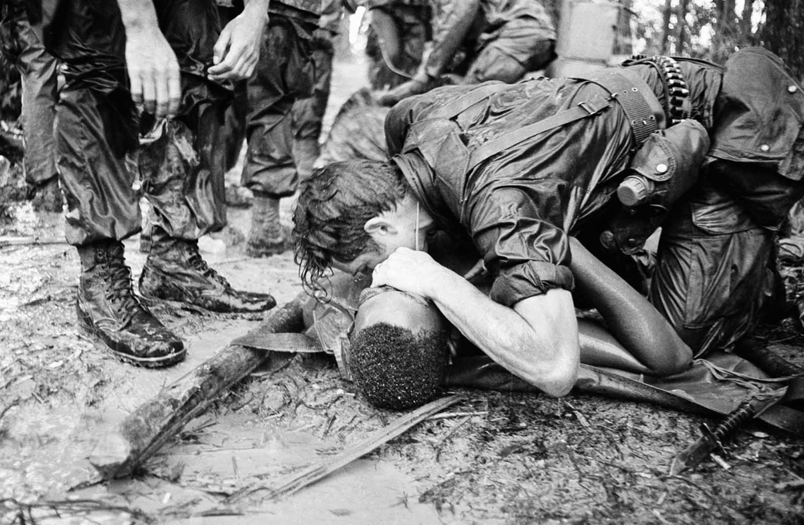 A trooper of the 101st Airborne Division attempts to save the life of a buddy at Dong Ap Bia Mountain, near South Vietnam's A Shau Valley on May 19, 1969. The man was seriously wounded in the last of repeated attempts by U.S. forces to capture enemy positions there.