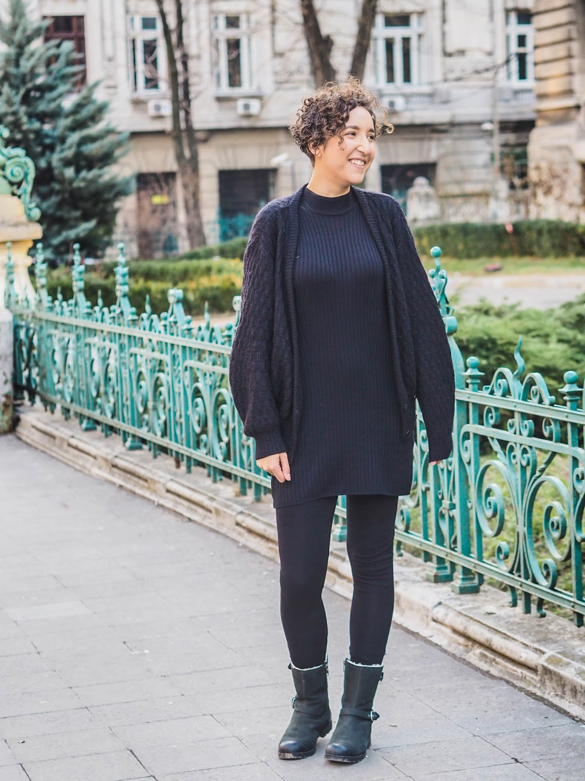 Fashion blogger wearing black dress, black cardigan, black boots