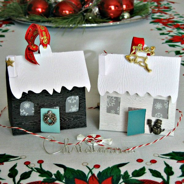 Two tiny paper houses decorated as a Christmas centerpiece