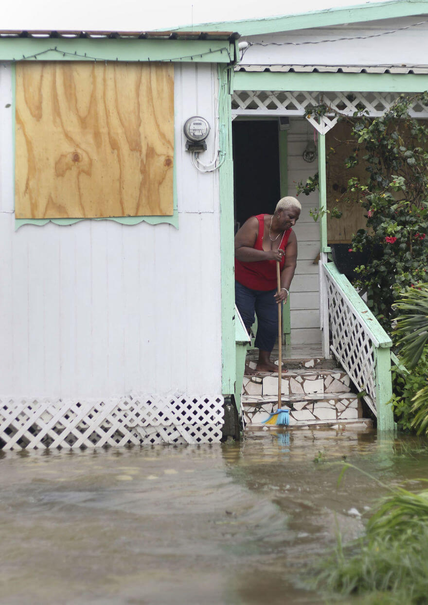 30 Shocking Pictures That Show How Catastrophic Hurricane Irma Is - A Woman Pushes Out Floodwaters On Her Property After The Passing Of Hurricane Irma, In St. John's, Antigua