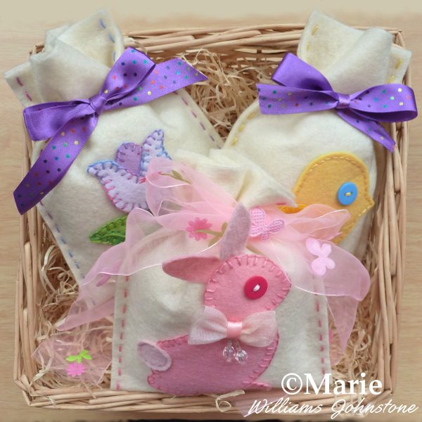 Felt Easter bags pink bunny spring chick and tulip flower design patterns tied with ribbon and displayed in a basket