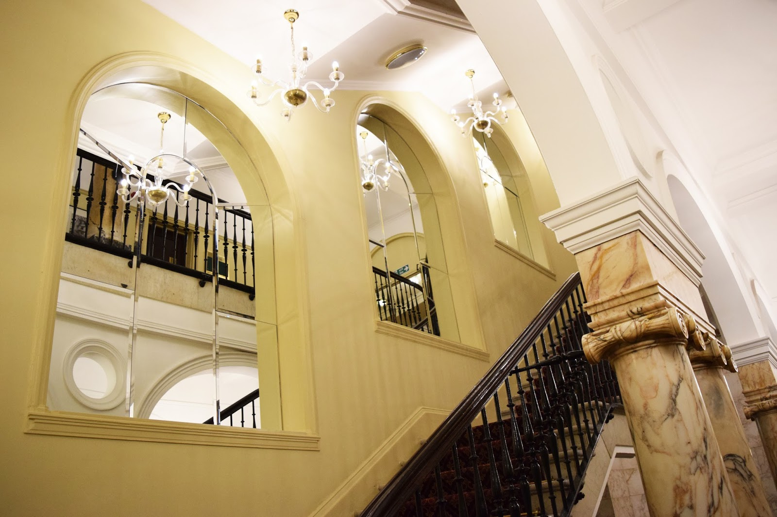 the grand staircase which runs throughout the hotel. Large mirrors can be seen in places of windows