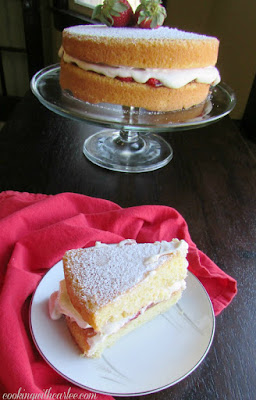 slice of victoria sponge cake with remaining cake on pedestal in background