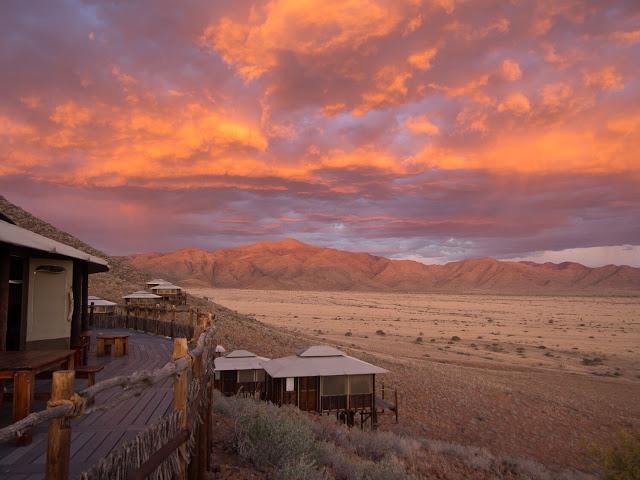"""Namibia – vùng đất bị bỏ rơi, khắc nghiệt và cháy nắng, vùng đất chu du của mặt trời thách thức những giới hạn con người. Phủ đi những nét mờ nhạt của cấu trúc chưa hoàn thiện, Namibia tự """"tô"""" thêm cho mình mảng màu lộng lẫy giữa sắc trắng của chân trời, màu xanh của mây hòa trong sắc đỏ ngã nâu của ánh mặt trời vừa ló mỗi sáng hay lụi tắt mỗi chiều. Cung đường của bạn sẽ tuyệt vời nhất vào bình minh và hoàng hôn. Thử ngừng bánh, leo lên nóc xe, thỏng chân mà ngắm nhìn mặt trời đang tràn ra, tráng hồng cả vùng trời rộng lớn."""