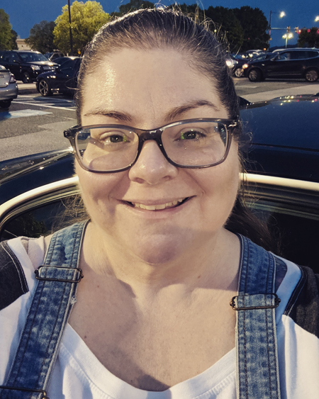 image of me from the shoulders up, standing in a parking lot at dusk, smiling, my hair pulled back into a bun, wearing grey-framed glasses, a ringer tee, and denim overalls