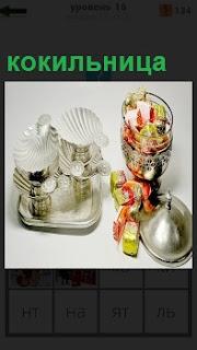 Изображение кокильницы и вазы рядом с разными угощениями,перевязанные ленточками