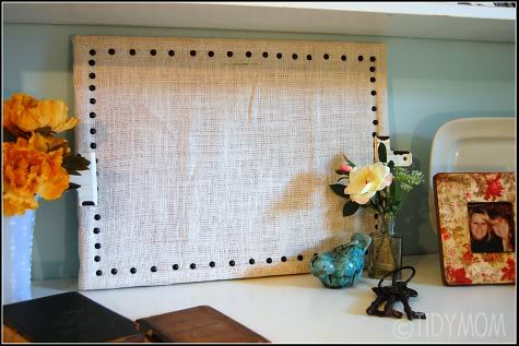 This DIY bulletin board is made with burlap wrapped around a corkboard. Perfect for your office!