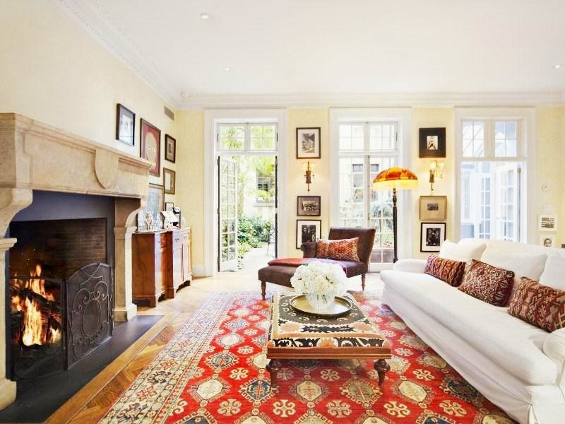 Living room in a NYC home with white sofa, Persian rugs, herringbone wood floor and marble fireplace