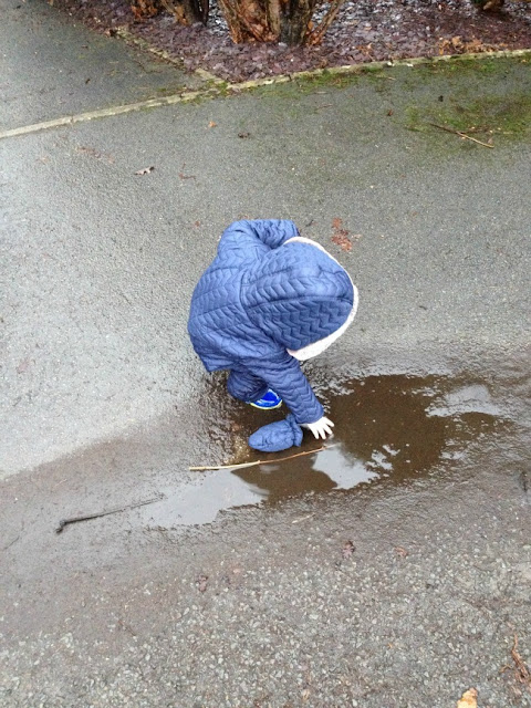 toddler putting hand into a puddle