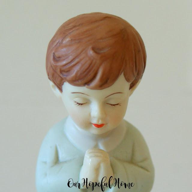 porcelain little boy brown hair blue suit red lips praying