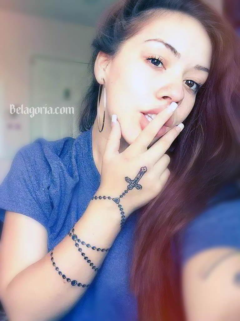 Una preciosa modelo con un tatuaje de pulsera de rosario
