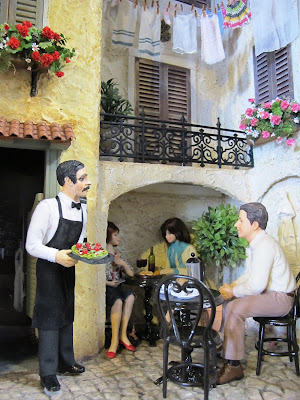 One-twelfth scale miniature scene of a European courtyard with a waiter serving diners.