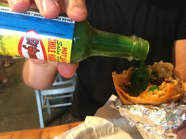Lurid green hot sauce on burrito time!