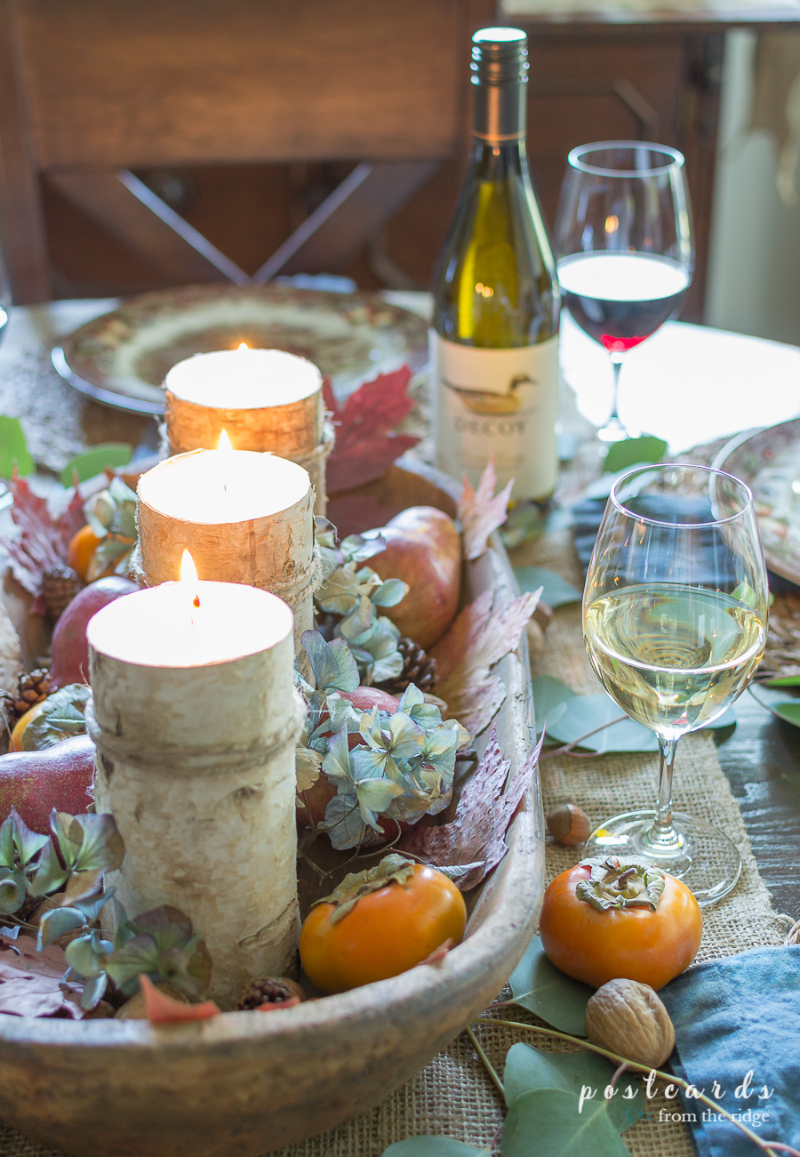 birch-wrapped candles with dried hydrangeas, persimmons, and natural elements