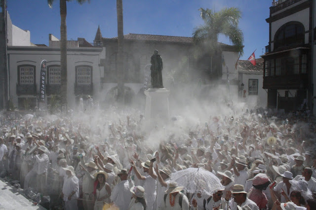 Lots of people wearing white throwing talcum powder.