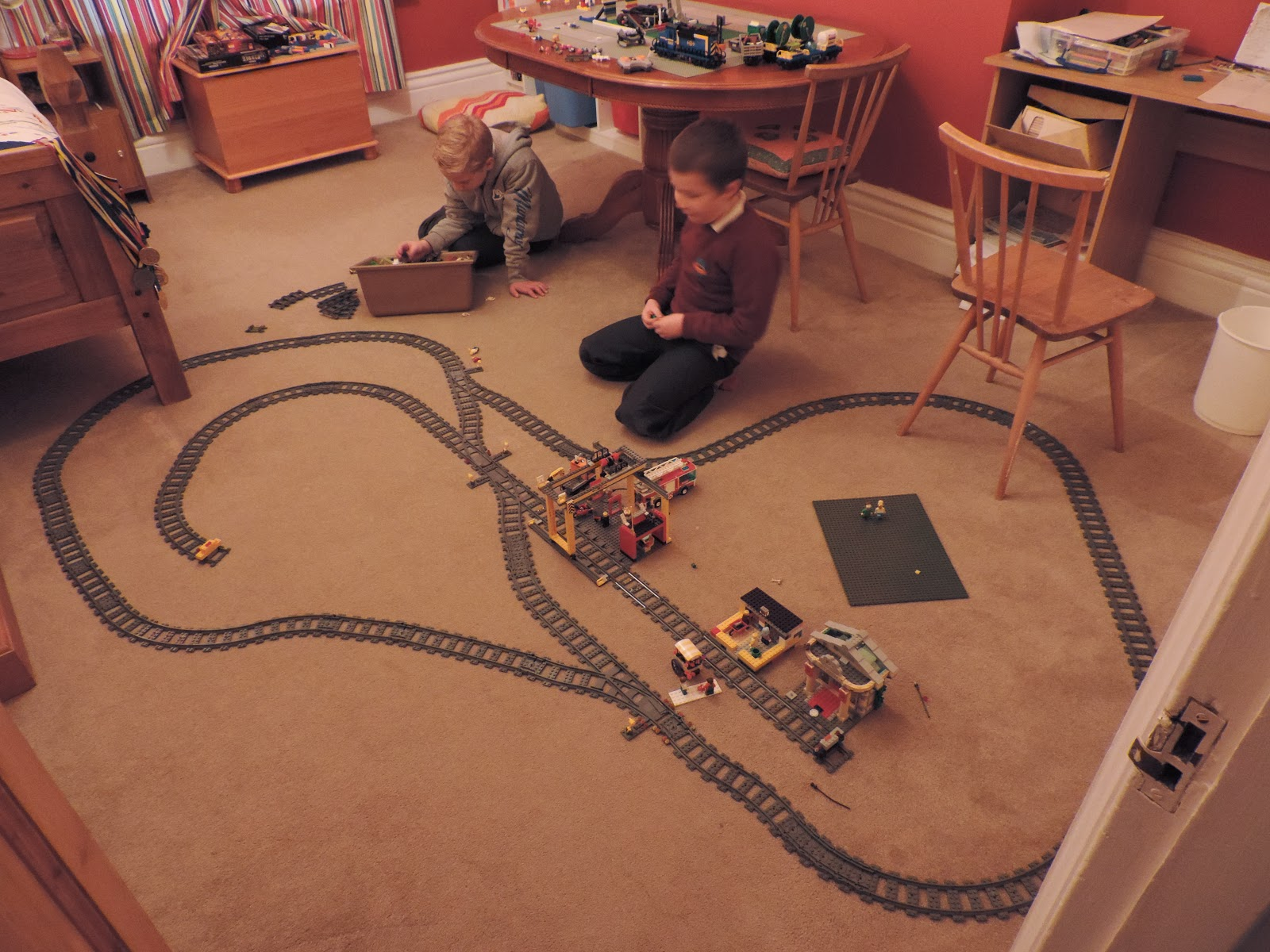 boys playing lego trains on bedroom floor