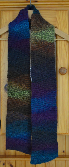 Shadow Spectrum slip stitch scarf on a coathanger hanging on a pine dresser.