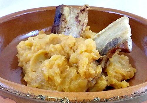 Un plato de barro con patatas con pimentón coronado con panceta