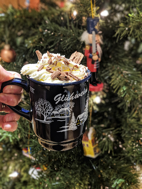 Hot chocolate mug in front of Christmas tree