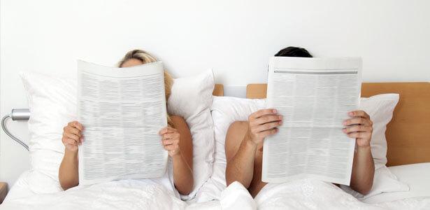 Pareja en la cama leyendo el periodico