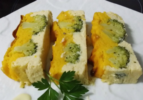 Pastel de color blanco y amarillo con el brocoli entero en medio
