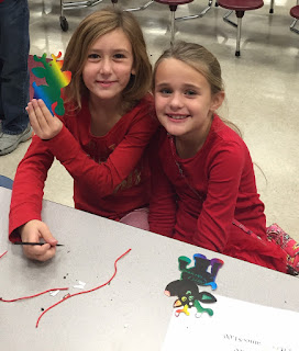 Two young girls in red shirts working on a craft