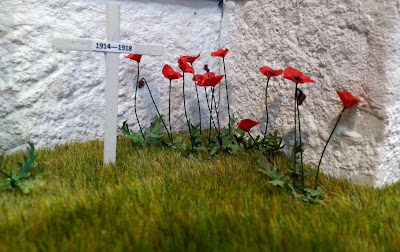 One-twelfth scale miniature poppies and crosses planted in a lawn.