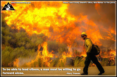 To be able to lead others, a man must be willing to go forward alone. – Harry Truman (Wildland firefighter walking on a road next to a raging wildfire)
