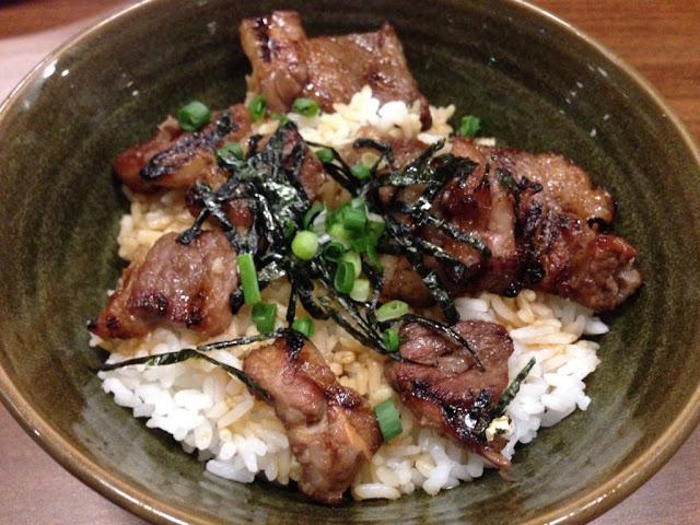nasi putih yg ditaburi potongan daging sapi panggang