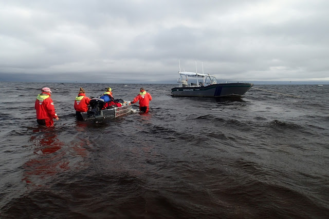 Neljä henkeä pelastautumispuvuissa kahlaa kohti isompaa venettä ja työntää mukanaan pikkuvenettä lastattuna täyteen varusteita