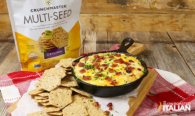 multigrain crackers surround bacon and cream cheese dip recipe in cast iron skillet