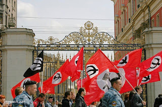 Marchers carrying flags with black hammer and sickle in a white circle on a red field