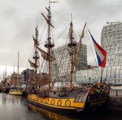 Photo of the old sailing boats contrasting with the modern architecture