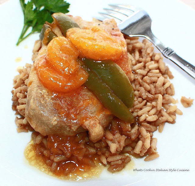 A delicious mandarin orange, peppers Asian sauce with boneless pork pour over rice in a white plate.
