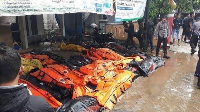 Petugas gabungan dan warga mengevakuasi korban tsunami.