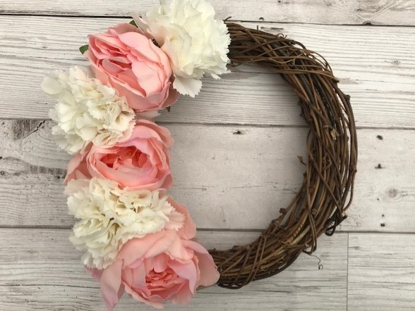 Rattan wreath with flowers along one side