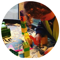 builder tuff tray with duplo bricks, diggers, shaving foam cement and a trowel