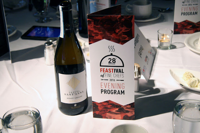 Program for FEASTival and a bottle of win on the table