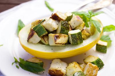 Zucchini-Halloumi-Gröstl in der Melone serviert