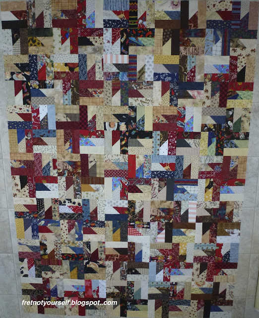 Western fabrics in red, black, brown and blue alternating with white and tan fabrics create the windmill shape of the block.
