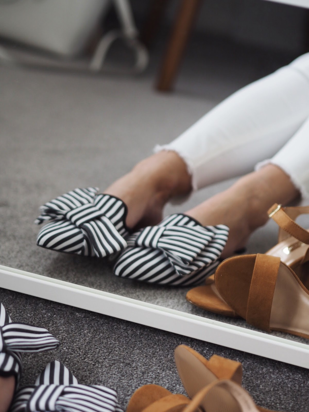 Striped Mules on legs with white jeans infront of a mirror for reflection