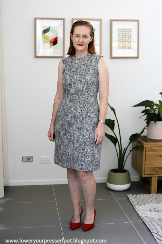 woman modelling a grey fitted dress in front of plants