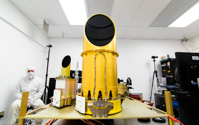 The University of Arizona's camera suite, OCAMS, sits on a test bench that mimics its arrangement on the OSIRIS-REx spacecraft. The three cameras that compose the instrument – MapCam (left), PolyCam and SamCam – are the eyes of NASA's OSIRIS-REx mission. They will map the asteroid Bennu, help choose a sample site, and ensure that the sample is correctly stowed on the spacecraft. Photo Credit: University of Arizona/Symeon Platts