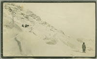 A photograph of Melville Island, primarily a large snow-covered mountainside with several small figures at the mid-right and one tiny individual standing in the lower left corner of the frame.