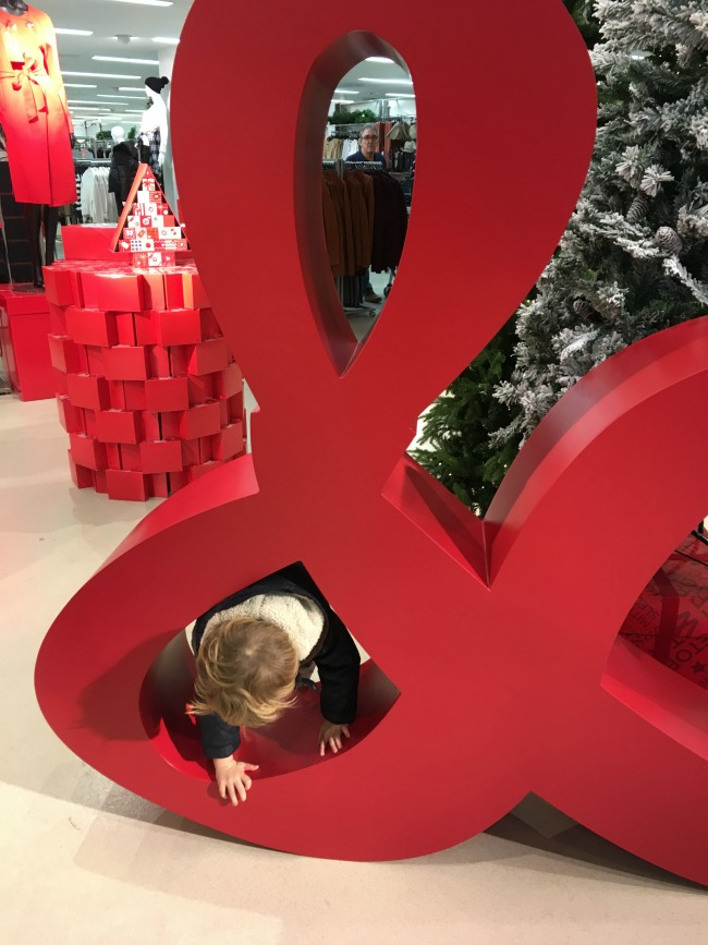 toddler-climbing-through-ampersand-at-marks-and-spencers