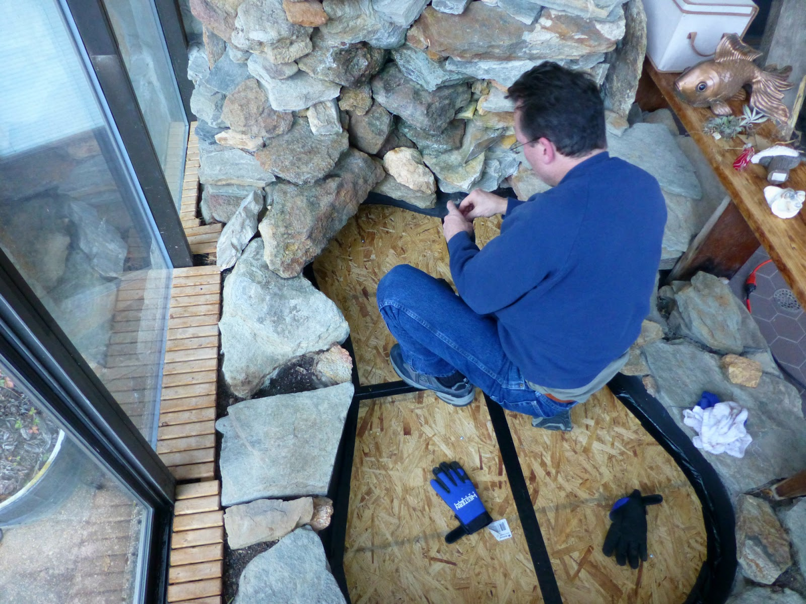 2016 Winter Projects at our Asheville area B B Man applying duct tape to plywood seams in fishpond